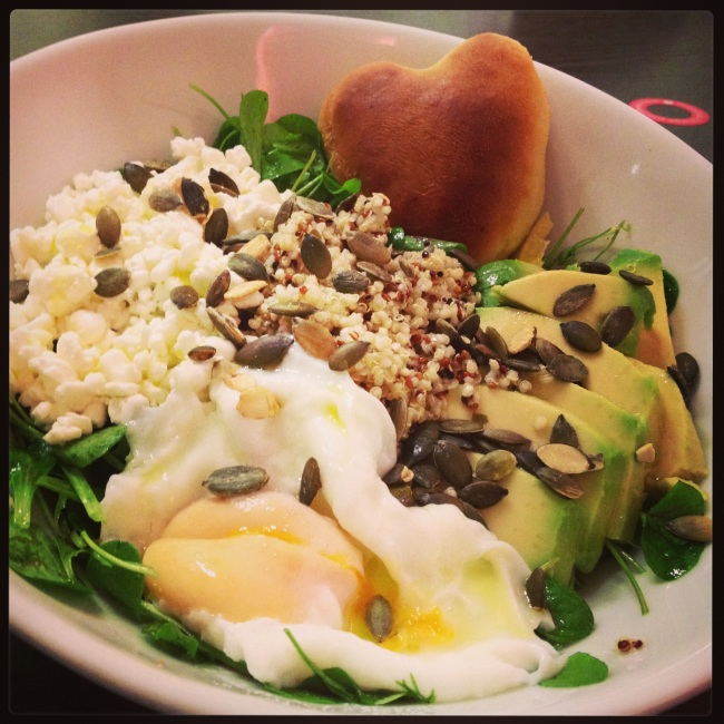 A made to order salad with quinoa, avocado, poached egg, cottage cheese and pumpkin seeds...served with a heart shaped focaccia roll.